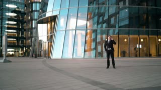 Funny joke. Young businessman have a smartphone talking. Goof stupid competitor running and giving kick ass to suit clothes man and runs away. Businessman overtake rival. Glossy business centre
