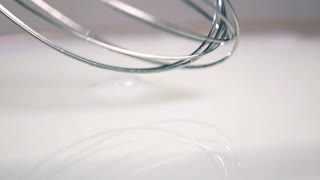 High-speed shot of whisking absolutely white milk with digital blender. Big splashes of liquid. Slow motion 20 times. 500 fps