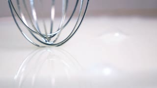 High-speed shot of whisking absolutely white milk with digital blender in vertical position. Slow motion 20 times. 500 fps