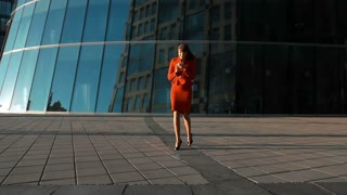 Joyful sexy businesswoman in red suit and smart phone in euphoria of winning the deal next to the skyscraper in business district, slow motion shot at 240fps, steadycam shot