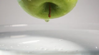 LIttle drop of water falling down from the fresh green apple into the water with small circular waves and little splash. Super slow motion shot on Sony rx 10 ii, white background isolated