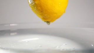 Macro view of drop of water dripping from the fresh yellow lemon on the water surface with little waving splash. Gray background isolated shooting in super slow motion mode on Sony rx 10 ii