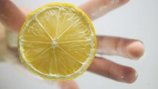 Man hand pulling half of tasty fresh yellow lemon from transparent water with little wavy splash, breaking the surface of liquid. Underwater high-speed slow motion shot on white background isolated