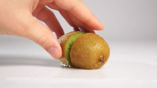 Man hand taking fresh kiwi half on two halfs on wet white surface. Shooting with high-speed camera in slow motion mode. White background isolated