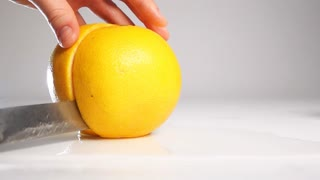 Man hand with big steal knife cutting fresh grapefruit on two halfs on wet white surface. Right half rolling onto its side. Shooting with high-speed camera in slow motion mode. Gray background