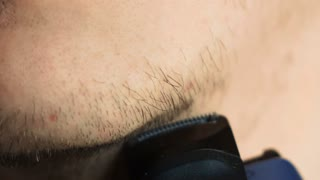 Man shave chin with electric shaver in slowmotion
