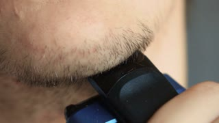 Man shave chin with electric shaver