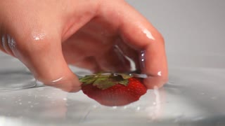 Man's hand drop out fresh tastyred strawberry with green top into water breaking liquid surface with little splash. White background isolated. Super slow motion camera horizontal shot