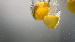 Parts of lemon drops under water. Grey Background