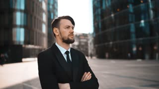 Portrait of young confident successful attractive caucasian business person with beard and mustache, arms crossed, looking at camera serious. Businessman. Success concept. Formal black suit, tie