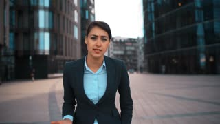 POV. Portrait of young attractive sexy caucasian businesswoman Swear and cuss on You. Pomade, brownhair, lady. Negation concept. Blackguard abuse. Formal suit. Modern glass buildings bg. Sunrise. Teal