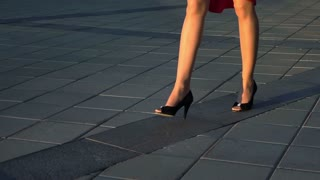 Sexy woman legs in black high heels shoes walking in the city urban street. Steadicam stabilized shot Slow motion. Red suit. Cinematic teal and orange sunset shot