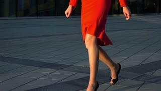 Sexy woman legs in black high heels shoes walking near glass business centre. Steadicam shot. Slow motion. Red suit, spectacles. Cinematic teal and orange sunrise shooting