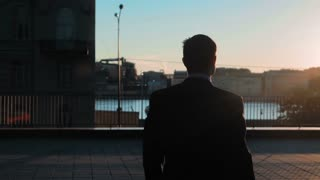 Silhouette of Young successful Businessman wins big deal with digital pad. Hands on. Outdoors on the business centre roof with city view. Slow motion shooting close-up