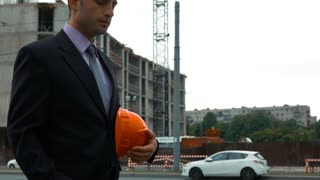 Slow motion. Attractive engineer answering call. He is holding helmet in arm, smiling. The man is wearing a suit and a hardhat. Crane and beams at the background. Middle shooting