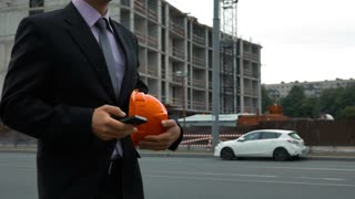 Slow motion. Attractive engineer is talking the phone. The man is wearing a suit and a hardhat. New building Construction with crane and beams at the background. middle shooting