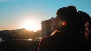 Slow motion. Beautiful young successful business woman turning around and looks very happy and fun sunrise. Steadicam sunset close-up. Blue clean sky. Hair fluttering on wind. Teal and orange style