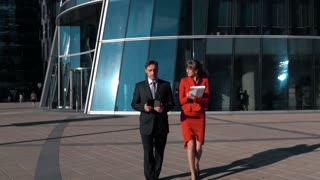 Slow motion: Business couple male and female walking near business centre bright sun. Man with ipad digital pad, woman with paper plane table writing instructions. Wide steadicam shooting