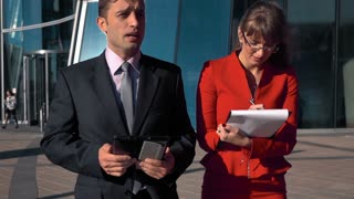Slow motion: Business couple male and female walking near businesscentre bright sun. Man with ipad tablet pc, woman with paper plane table in spectacles writing instructions. Middle teal orange shot