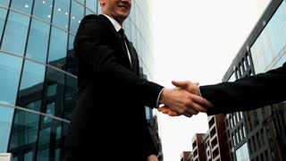 Slow motion. Businessman partners shaking hands beginning their partnership with modern glass building at the background. Teal and orange