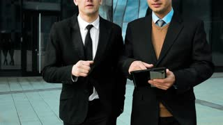 Slow motion: Discussion of two businessmen walking near office building. Using tablet computer to better handle the arguments. Teal and orange