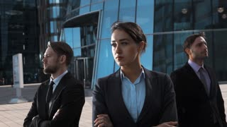 Slow motion. epic shot of three attractive confident businesspeople seriously look at camera. Sexy lady pomade brownhair front. Stand arm crossing modern building district bg. Teal and orange. Sunset