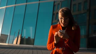 Slow motion. Euphoric sexy woman in red suit and glasses watching her smart phone read message, exulting and happiness of winning the great deal with glass modern business centre buiding at the bg