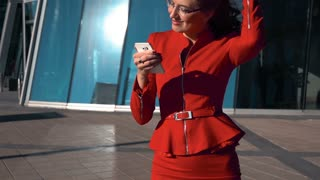 Slow motion: fashion close up portrait of young sexy woman with smartphone walking in street wearing red suit dissolve hair. Glass business centre. Midday. Steadicam shooting