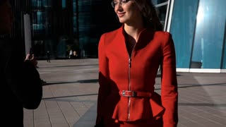 Slow Motion: Flirting of a business people outdoors, male and female in sexy red suit and glasses look at each other. Tablet pc and smartphone. Glass office building