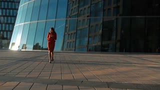 Slow motion of beautiful businesswoman in red suit using smart phone. Confident professional is on call. She walking standing outside glass office modern building in business district. Wide shot