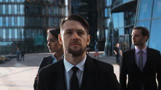 Slow motion. Portrait epic cinematic georgious shot of 3 seriously attractive confident businessmen and businesswoman looking at camera stand arm-cross. Sunset lighting. Brave Barber front person
