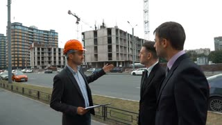 Slow motion. Presentation of the business plan of the new building. Three confident businesspeople. Architector with text tablet in helmet presents to customers their building