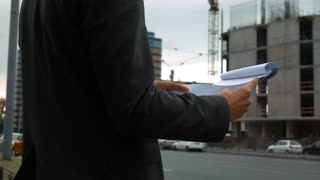 Slow motion. Project manager checking clipboard construction plan with newly constructed building with crane and beams at background. Detailed close up of text pad