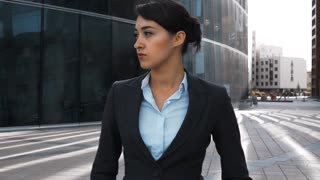 Slow motion. Sexy attractive businesswoman wearing formal suit and looking seriously from left then to camera. She walk near modern glass business centre district. Portrait steadycam sunny afternoon