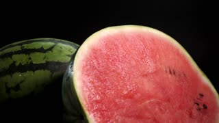 Slow motion. Sliced fresh tasty wet green stripet watermelon with red pulpy fruity juicy rich succous watermelon with red pulpy on black background. Ossicles and bones. Closeup rolling arround shot