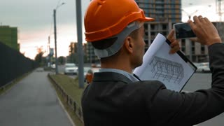 Slow motion. smart young attractive construction engineer with the smart phone taking pictures of objects on a construction site with beams and crane. Text tablet, orange helmet. Back close-up