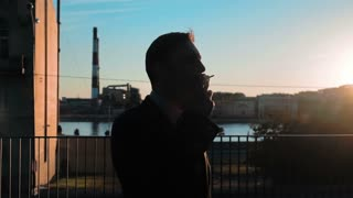 Slow motion. Sunrise silhouette of businessman smoking cigarette at the business centre roof. River and manufacture at the BG. Teal and orange. Middle steadycam shooting