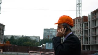 Slow motion. The builder in orange helmet alone talking on a mobile phone. Boss of a builders is giving orders on his mobile phone. Middle shooting with construction new building bg with crane and