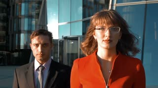 Slow motion. Two business colleagues walk near modern glass building, woman in red suit and spectacles, man in black. Teamwork concept. Teal and orange. dji ronin middle shooting