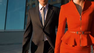 Slow motion. Two business colleagues walking against office building, experienced businessman and businesswoman professional colleague while looking to you, teamwork concept