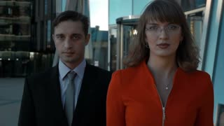 Slow motion. Two business colleagues walking in business centre district, woman in red suit and glasses, man in black. Teamwork concept. Teal and orange. Stabilizer middle shot. Look at camera