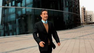 Slow motion: two businessman partner in suit shaking hands with smile. Glass business centre building at background. Close-up steadycam shooting