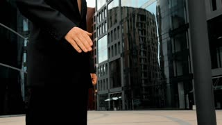 Slow motion. Two businessmen shaking hands with modern glossy building at the background. Middle steadycam shot. Teal and orange style