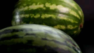 Slow motion: two fresh striped green huge big tasty watermelons at black surface and bakground. First slowly rolls by the floor. Middle shooting tripod