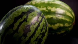 Slow motion: two fresh striped green huge big tasty watermelons at black surface and bakground. First slowly rolls by the flor from left to the ritht