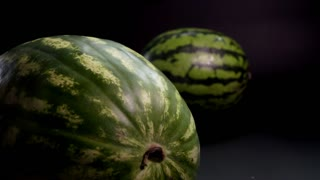 Slow motion. Two Green huge fresh wet tasty striped Watermelons slider skating and rotation on a black background and surface. close-up shooting. Ossicles and bones