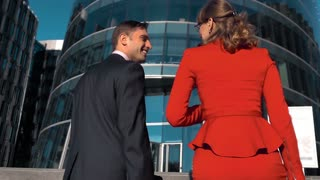 Slow motion. Two young business people discussing outdoor with glass building bg. Male and female, man and woman. Smile. Middle steadycam shooting
