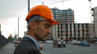 Slow motion. Young attractive builder in a orange helmet is making call on the mobile phone. unconstructed building with crane at the background. Close-up steadicam shooting