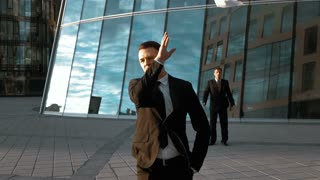 Slow motion. Young businessman throwing some paper sheets in the air with cityscape in the background rejecting partner offer. Middle steadicam shot