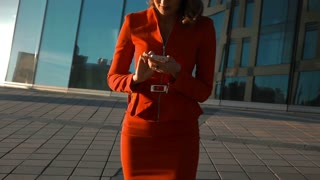 Slow motion: Young sexy business woman in red suit and glasses answering call with smart phone. Teal and orange style. Business-centre district background. Steadicam shot